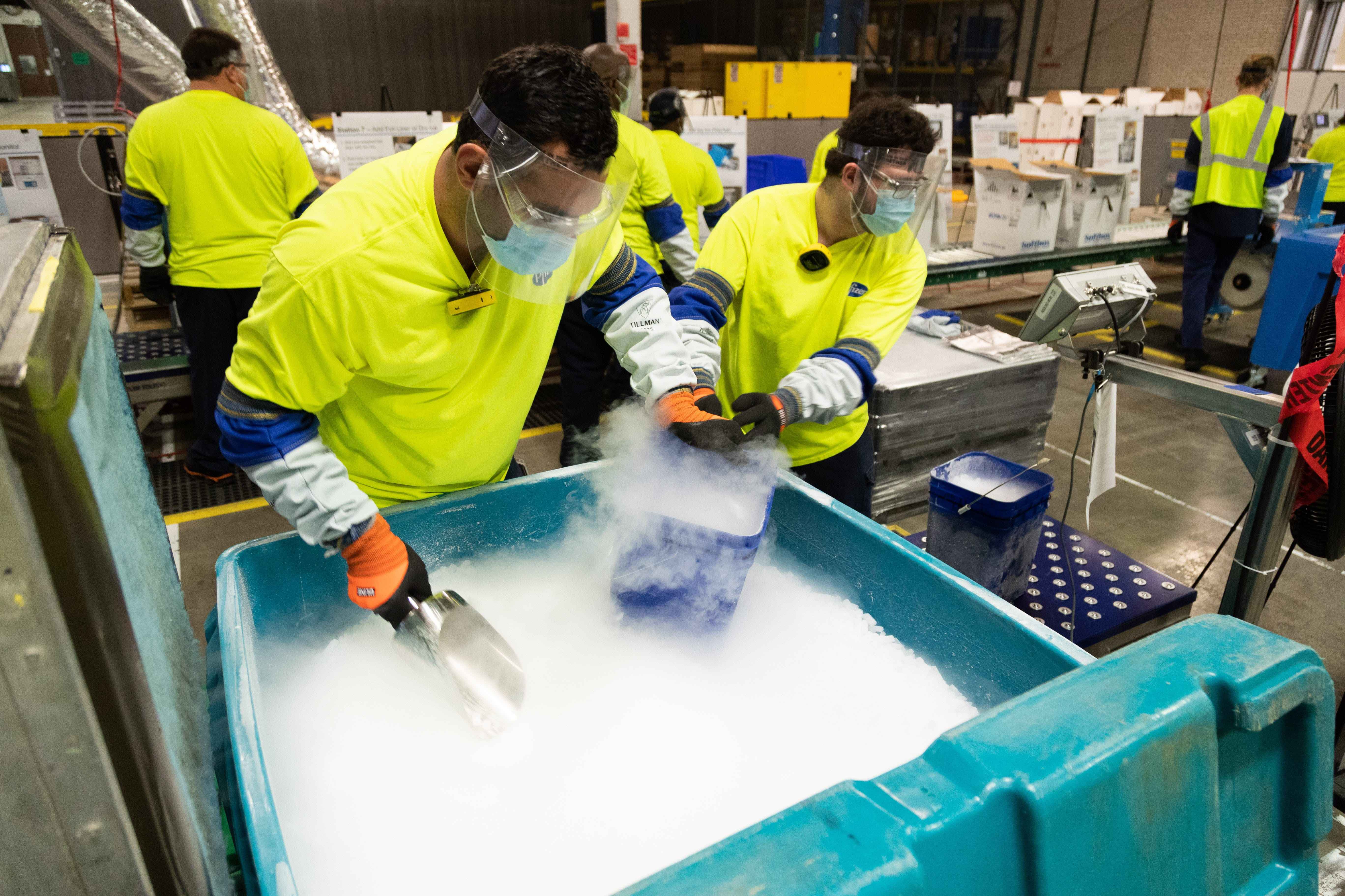 Workers at Pfizer's manufacturing site in Kalamazoo, Michigan, fill buckets with dry ice that will be poured into thermal shipping containers holding the COVID-19 vaccine. The thermal shippers are used to ship vaccines from Pfizer plants to their intended destinations at the required subzero temperature.