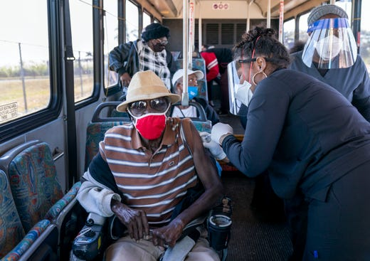 A senior receives a COVID-19 vaccine from a health care worker after arriving on a bus to a vaccination site at Anquan Boldin Stadium in Pahokee, Fla., on Feb. 3.