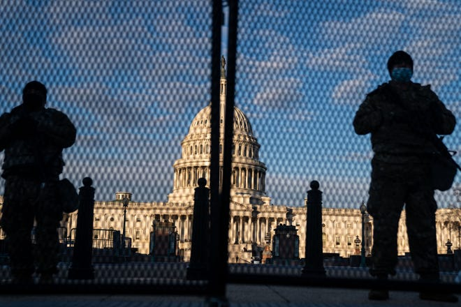 National Guard troops stand behind security fencing with the dome of the U.S. Capitol Building behind them on  Jan. 16, 2021, in Washington, D.C. [Kent Nishimura/Los Angeles Times/TNS/File]