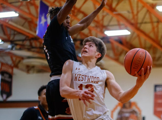 Westwood Warriors forward Zach Engels, right, drives for the layup against defending Hutto Hippos forward Joemori Francis during the first period at the District 25-6A boys basketball game Feb. 4 at Westwood High School.