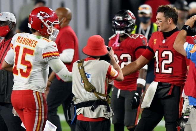 Tampa Bay Buccaneers quarterback Tom Brady (12) congratulates Kansas City Chiefs quarterback Patrick Mahomes (15) after their NFL football game in Tampa, Fla. The Super Bowl matchup features the most accomplished quarterback ever to play the game who is still thriving at age 43 in Brady against the young gun who is rewriting record books at age 25.  (AP Photo/Jason Behnken, File)