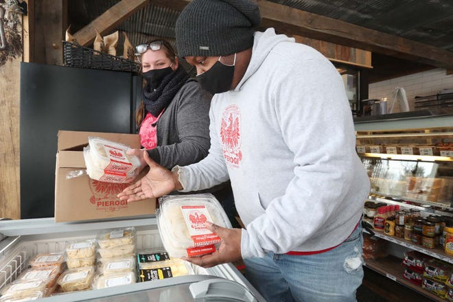 Autumn Johnston, left, and Marcus Walker, owners of The Pierogi Lady, replenish their pierogies in a freezer case at The Farmer's Rail while dropping off an order to the market and butcher shop last week in Bath.