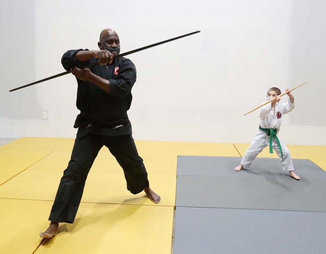 Reggie Brown, left, the owner and sensei of the Twinsburg Karate Institute, works with student Carter Roesel, 8, on learning the basics of bo kata.