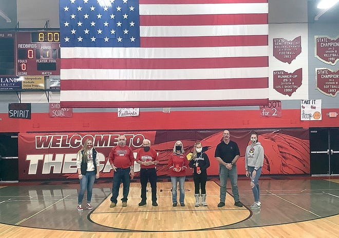 Loudonville High School LEO Club President Sydney Snyder, American Legion Riders Vice President Randy Hinkle, Cowen Truck President Bob Cowen, Mohican Adventures CEO Patty Shannon and Halaina Grey, LHS LEO Club Advisor Jeff Frankford, and LHS LEO Club Vice President Grace Vermillya pose with the American flag in the LHS gym.