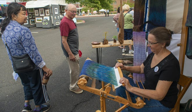 Kathy Dinsmore, left weaves as patrons pass by during the New Hope Arts and Crafts Festival on Sept. 28, 2019.