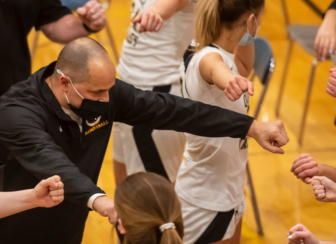 Quaker Valley High School girls basketball coach Tom Demko fist bumps his team after a timeout during the Quakers' game against Blackhawk on Thursday at Quaker Valley High School in Leetsdale.