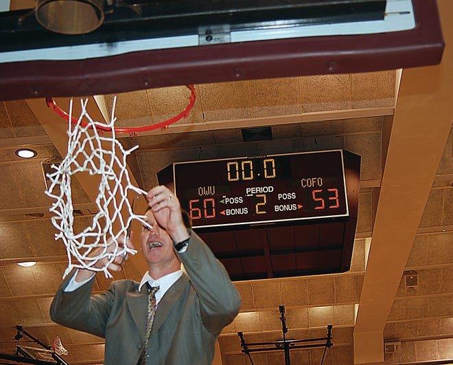 OKWU head coach Donnie Bostwick cuts down the net in March 2009, after his Eagles beat College of the Ozarks for the NAIA-II national championship.