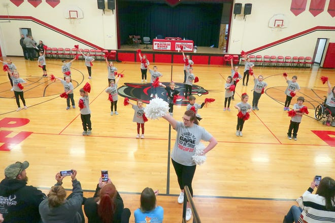 Senior cheerleader Madison Bishop leads a spirited group of students at the cheer clinic performance Friday night.