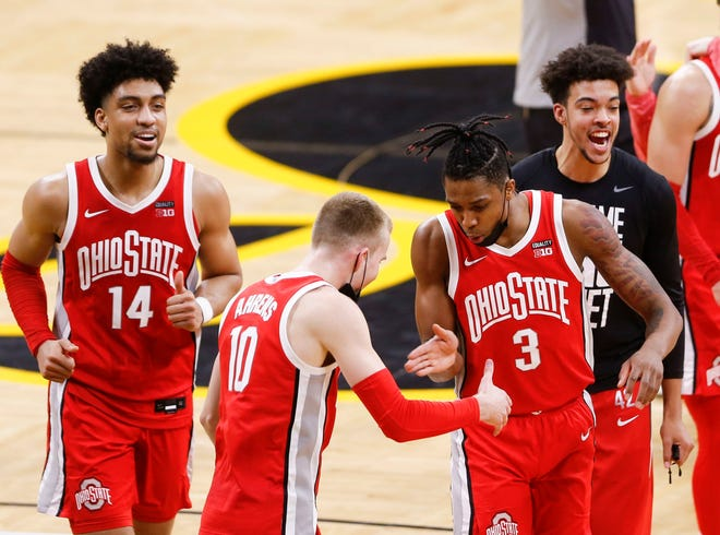 Ohio State forward Justin Ahrens (10) celebrates with Eugene Brown and his teammates after the Buckeyes' 89-85 victory at Iowa on Thursday.