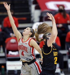Ohio State guard Jacy Sheldon slips past Iowa's Kate Martin to score two of her career-high 29 points in Thursday's victory over the Hawkeyes.