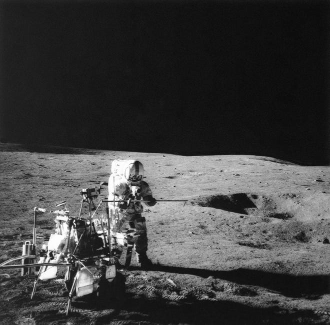 Apollo 14 commander Alan Shepard conducts an experiment near a lunar crater using an instrument from a two-wheeled cart carrying various test tools.
