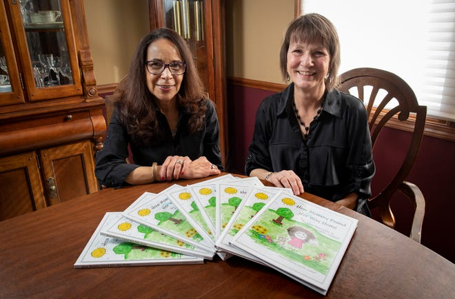 "Annette Dominguez, left, and Candace Paulucci sit with their self-published children's book, ""How Mommy Found Her Way Home,"" inside Dominguez's Gahanna home. The book is geared toward helping the kids of incarcerated women deal with having a mother in prison."