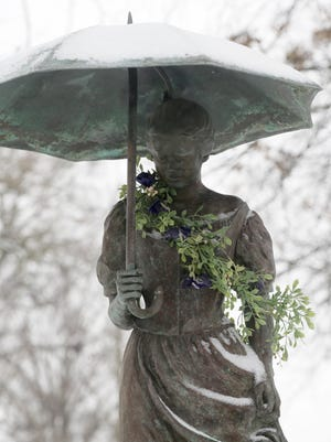 "Flowers were recently placed around the Umbrella Girl statue in Schiller Park in tribute to its model and inspiration, Andrea ""Andi"" Wobst-Jeney, who died  in Connecticut on Jan. 15. This week, the statue, which has become a beloved landmark and symbol of the neighborhood, was additionally adorned in a dusting of snow."
