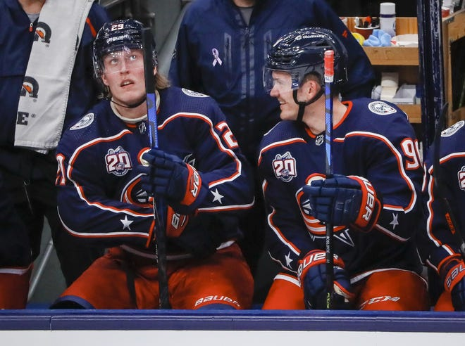 Blue Jackets forwards Patrik Laine, left, and Jack Roslovic share a moment on the bench in Thursday's win over Dallas. Both players scored their first goals for Columbus in the game.