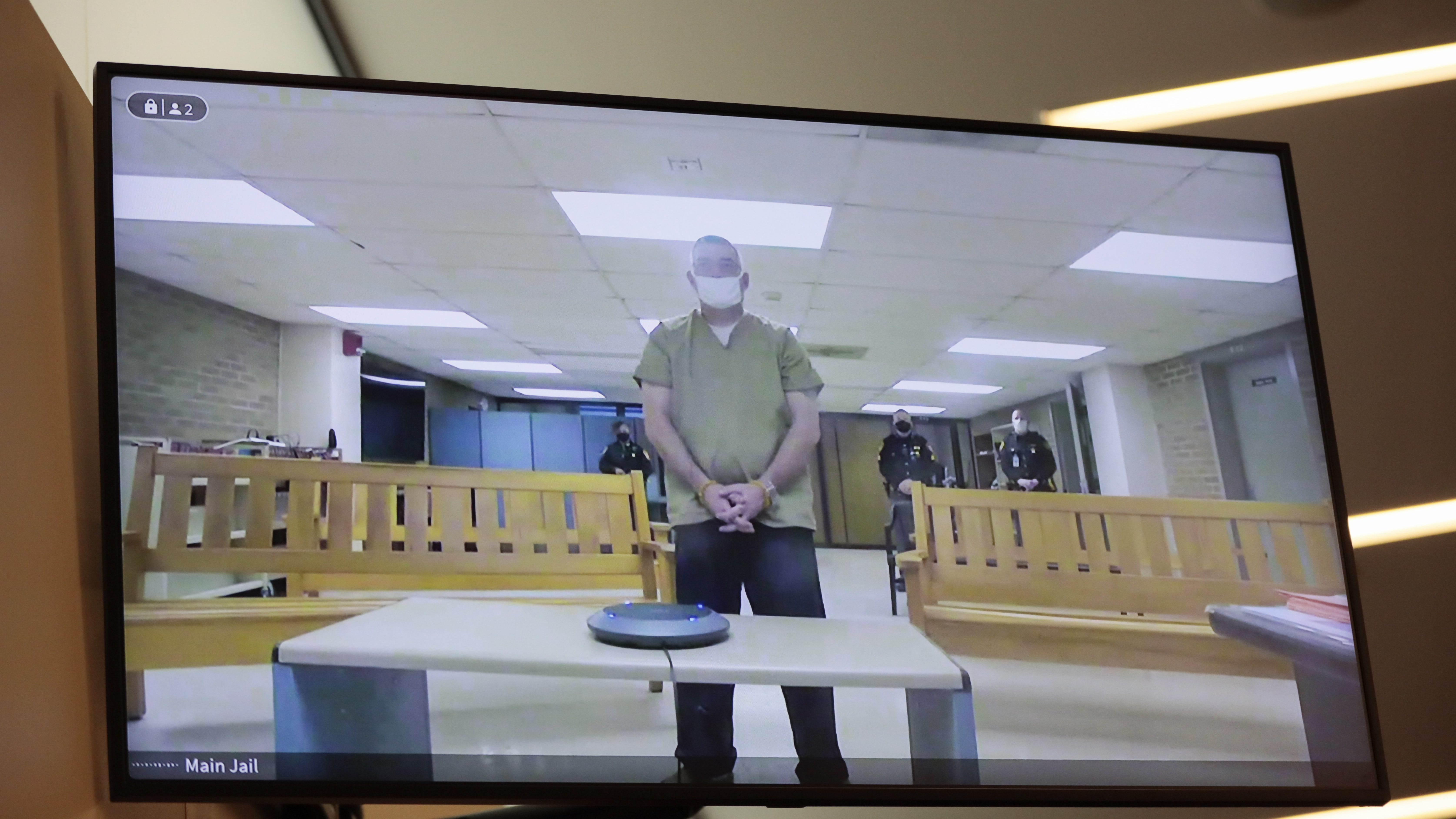 Former Columbus police officer Adam Coy is seen remotely on a television during his initial appearance on Friday, Feb. 5, 2021 at the Franklin County Common Pleas Courthouse in Columbus, Ohio. Coy was arraigned on four charges in the December 2020 police shooting death of Andre Hill, a Black man. Coy was charged with one count of murder, one count of felonious assault and two counts of dereliction of duty, one of which was for failure to render aid to Hill after he was shot. His bond was set at $3 million.