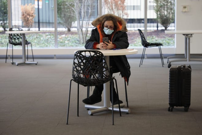 Linda Frazier checks her phone while inside a warming station on Dec. 22 at the Columbus Metropolitan Library's Main Library Downtown. The station opened for homeless people to have a respite from the cold weather.