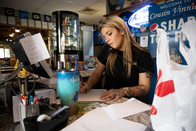 An employee takes an order for wings on Super Bowl Sunday. [Cindy Peterson/Correspondent]