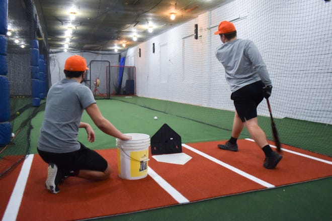 Meadowbrook High baseball players Damen Launder, left, and Hayden Loy get in some hitting practice at the newly-opened Batters Up in Byesville.