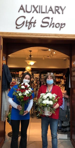 Hospital volunteer Alyssa Lubba, left, and Doris Bowman, auxiliary gift show manager, pose with some of the flowers available in the Wooster Community Hospital Auxiliary's Valentine's Day Floral Sale.