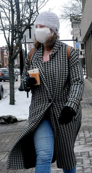 Laurie Judson sends a mixed message as the cold wind whips up her coat while she carries an iced coffee in downtown Wooster on Friday.