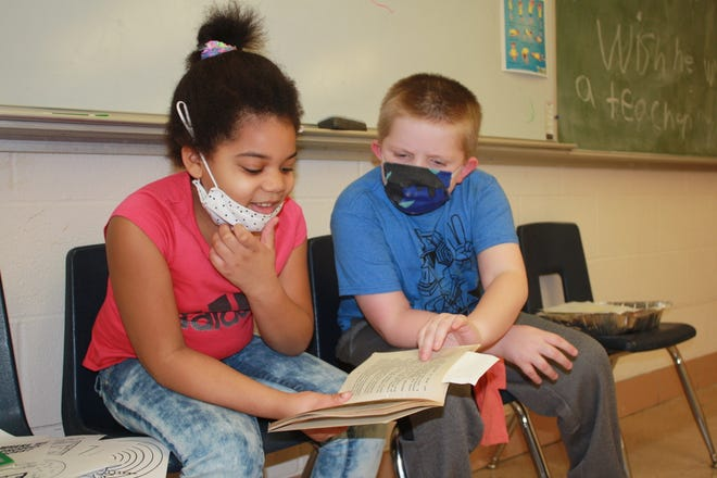 """Kyli Curry, 7, and Kory Taylor, 8, read aloud from the book """"Aliens Don't Wear Braces"""" in Tonya Blasor's classroom at James Madison Enrichment Center. Next week, Curry will return full-time to Grimes Elementary School, while Taylor will be at North Hill as the district resumes 100% in-person instruction."""