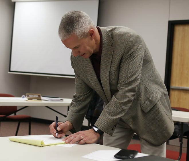 Dr. Trig Overbo signs his contract Thursday night to become the new superintendent of Glen Rose ISD.