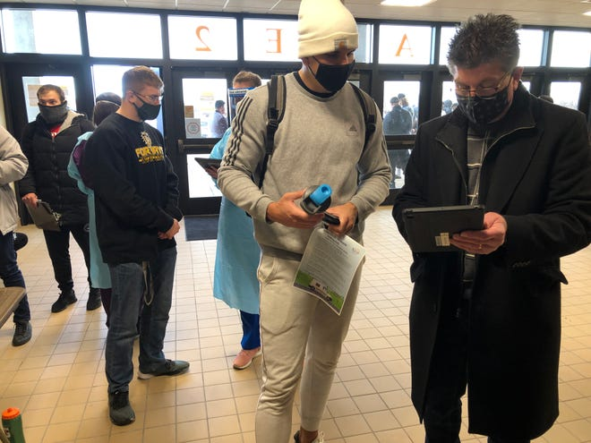 Myron Gunsalus Jr., director of the KDHE laboratories, right, checks in FHSU student Andre Aires, on Friday morning at Gross Memorial Coliseum in advance of COVID-19 testing.