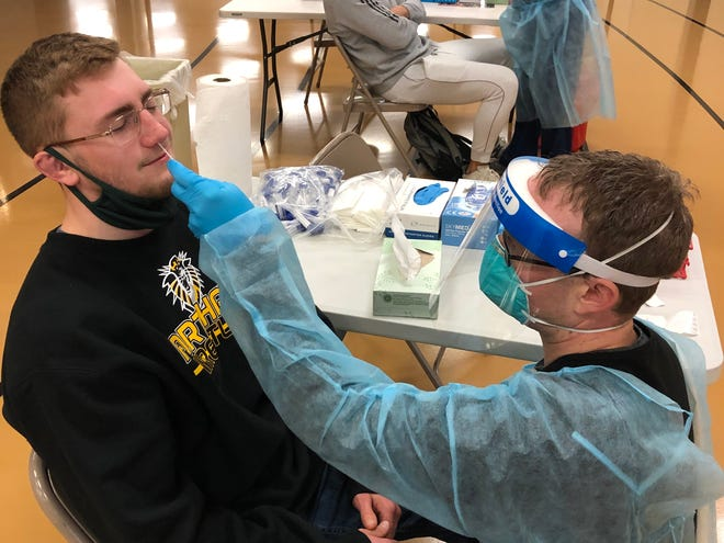 Fort Hays State University student Kadin Heacock, left, gets swabbed for COVID-19 testing by Kansas National Guard medic Spc. James Hawkins on Saturday at Gross Memorial Coliseum.