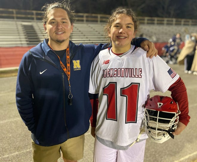 Jacksonville's Ryan Sullivan, right, and Northside coach Logan Sullivan get together after the Cardinals defeated the Monarchs 13-1 in a boys' lacrosse match Thursday night. [Chris Miller / The Daily News]