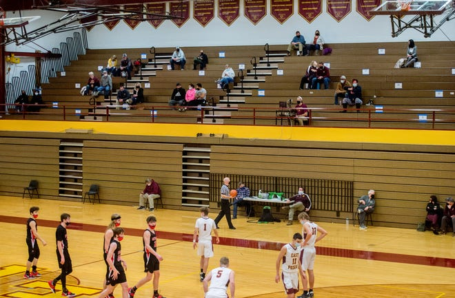 A small masked crowd stays socially distant on one of the gymnasium during a basketball game between East Peoria and Metamora on Thursday, Feb. 4, 2021 in East Peoria.