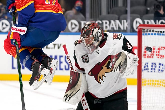 A puck is deflected by Arizona Coyotes goaltender Antti Raanta, right, as St. Louis Blues' Jaden Schwartz, left, leaps out of the way during the second period of an NHL hockey game Thursday, Feb. 4, 2021, in St. Louis.