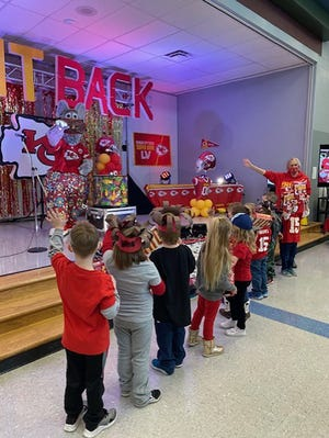Students wave to Kansas City Chiefs mascot KC Wolf on Friday at Pleasant Ridge Elementary School.