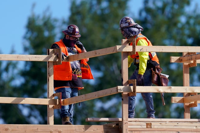 Construction workers talk at a USA Properties Fund site, Feb. 2, 2021, in Simi Valley, Calif. Hiring has weakened for six straight months.