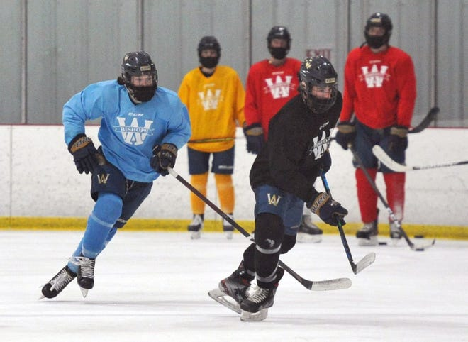 Archbishop Williams' John Riley (of Weymouth), left, and Nick Recupero (of Avon), right, go after a loose puck during boys hockey practice at the Canton SportsPlex, Thursday, Feb. 4, 2021.