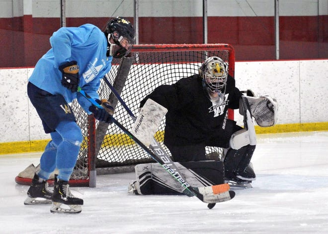 Archbishop Williams' James O'Toole of Rockland, left, takes a shot on goalie Brendan Carberry of Plymouth during boys hockey practice at the Canton SportsPlex, Thursday, Feb. 4, 2021.