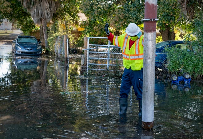A city worker vacuums water up from the ground after a water main break on Tamarind Avenue in West Palm Beach on Friday.