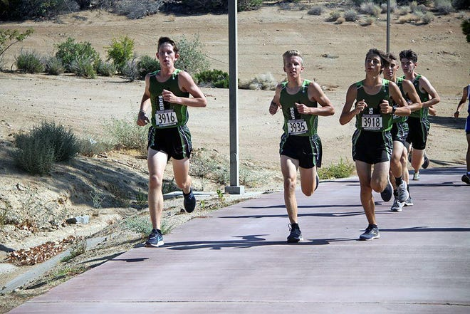 Bryce Hill, left, encourages his teammates to continue pushing during an invitational at Cerro Coso Community College in 2019.