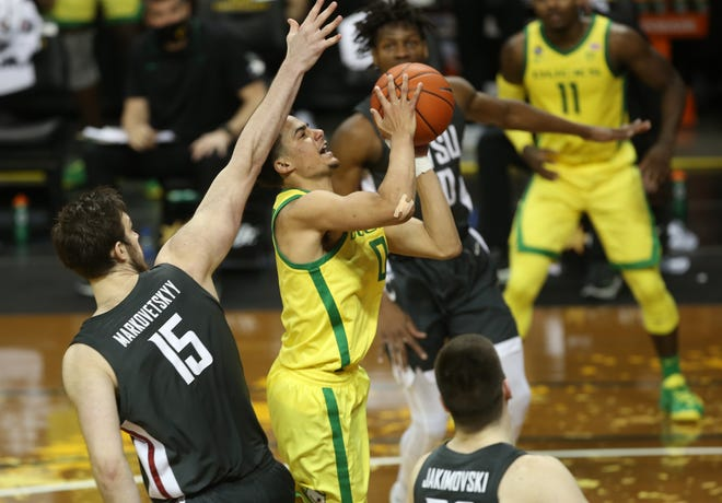 Oregon's Will Richardson, center, shoots in traffic against Washington State during the second half of Thursday's game at Matthew Knight Arena.