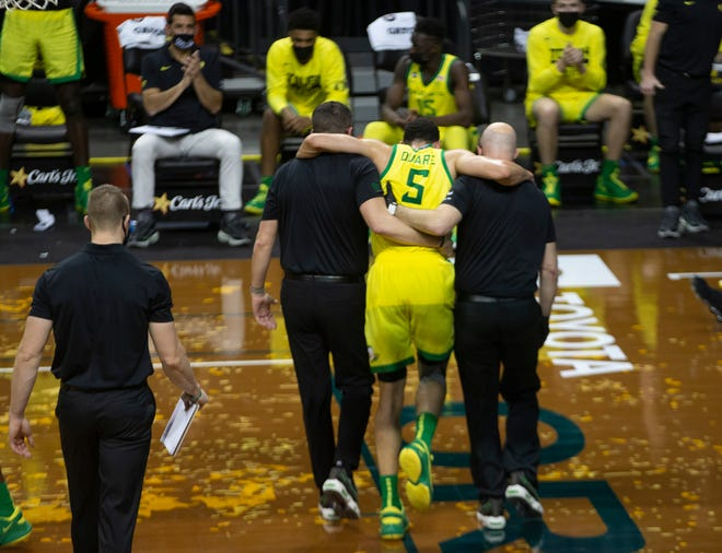 Oregon's Chris Duarte is carried off the court after an injury against Washington State on Thursday.