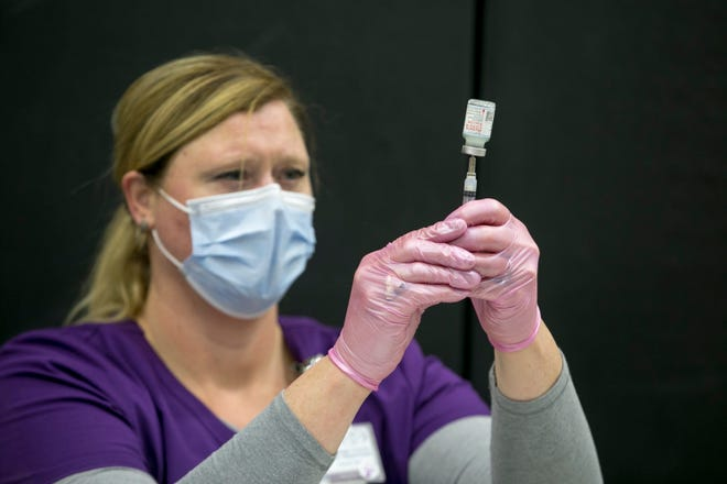 Christy Pohl, assistant director of public health service division of Winnebago County Health Department, prepares a dose of Moderna's COVID-19 vaccine at Auburn High School on Friday, Feb. 5, 2021, in Rockford.