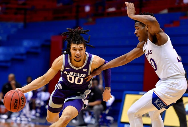 Kansas State guard Mike McGuirl tries to drive around Kansas' Ochai Agbaji during Tuesday night's game at Allen Fieldhouse in Lawrence.