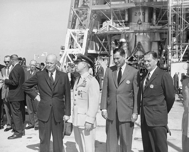 President Dwight Eisenhower is accompanied by two Defense Department chiefs as he tours the Cape Canaveral Missile Test Center on Feb. 10, 1960, in Cape Canaveral. Standing before a gantry housing an Atlas intercontinental missile are Eisenhower; Maj. Gen. Donald N. Yates, commandant of the missile center; Defense Secretary Thomas S. Gates Jr.; and Air Force Secretary William H. Douglas.