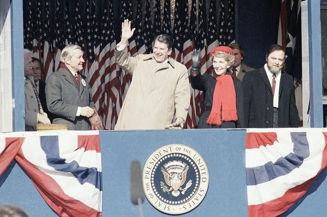 President Ronald Reagan and his wife, Nancy Reagan, second from right, wave from the reviewing stand during a birthday celebration parade through the streets of his boyhood home Feb. 6, 1984, in Dixon, Ill. The president celebrated his 73rd birthday.