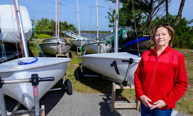 Barbara Dolan, former commodore of the St. Augustine Yacht Club, stands by some of the small sailboats the club uses in its youth sailing program on Thursday.