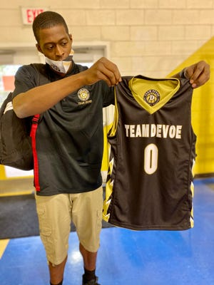 Danny Sanders Jr. holds up the new jersey of Team DeVoe, an AAU basketball team based in Cleveland County.