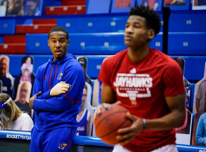 Kansas basketball freshman guard Bryce Thompson, left, watches teammate Ochai Agbaji warm up prior to the Jayhawks' game against TCU on Jan. 28 in Lawrence. Thompson, who is recovering from a broken right index finger, has missed eight of KU's last nine games.