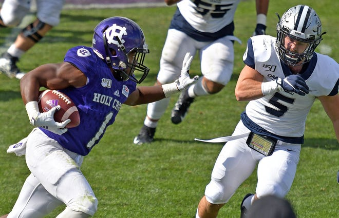 Holy Cross running back Domenic Cozier, left, runs past New Hampshire's Cameron Brusko during a game at Fitton Field in 2019.