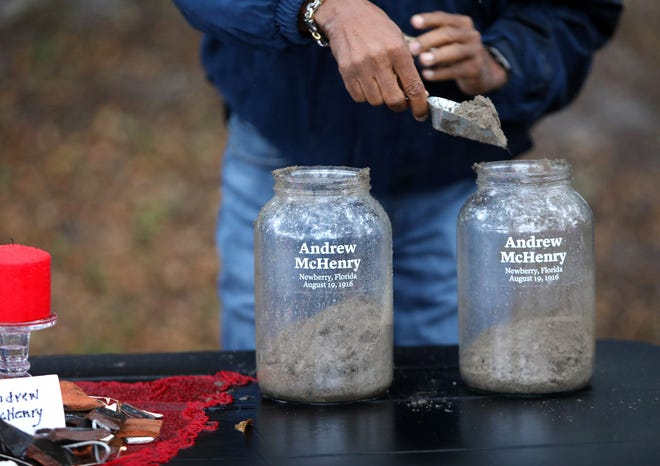 A man places a scoop of soil from the site of the Newberry Six lynchings in a glass jar with the name of one of the victims, Andrew McHenry, during a Soil Collection Ceremony at the site in Newberry on Feb. 5.