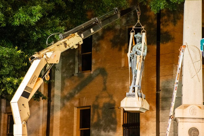 This photo shows the removal of a Confederate statue in Greenville, North Carolina, on Monday, June 22, 2020. Crews on Monday removed the bronze statue that tops the monument outside the Pitt County Courthouse in Greenville.  (Pitt County Public Information Office via AP)