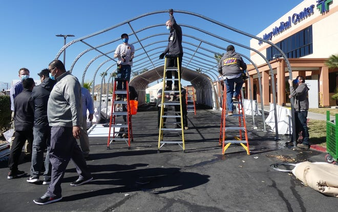 Crew members dismantle a triage tent used during the recent surge in COVID-19 hospitalizations outside Providence St. Mary Medical Center in Apple Valley on Thursday, Feb. 4, 2021.
